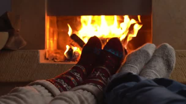 Couple in love wearing knitted woolen socks lying next to the fireplace