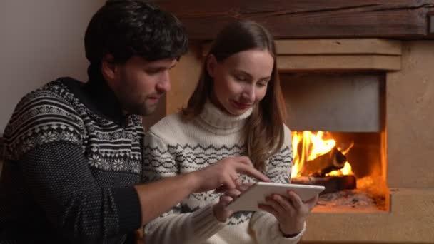 Usmívající se pár sedí na podlaze a doma u krbu používá tablet