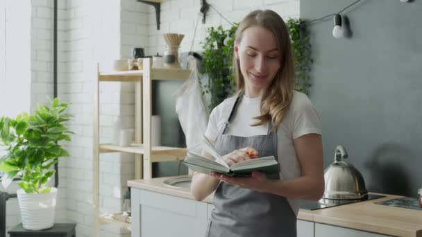 Mladá žena čte kuchařku v kuchyni, hledá recept
