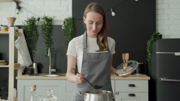 Glückliche Frau schmeckt Suppe aus der Kelle und lächelt in der Küche