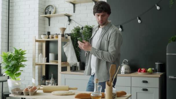 Férfi szörfözik az interneten a konyhában álló telefonnal. Portré férfi áll a konyhában, és használja okostelefon