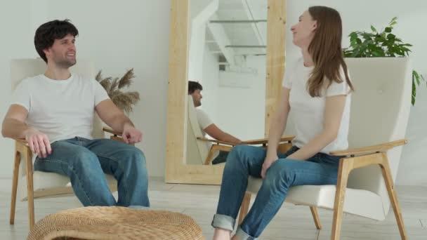 Schönes junges Paar spricht und lächelt, während es zu Hause auf Sesseln sitzt