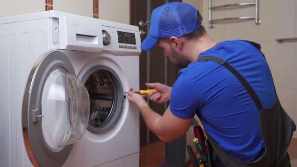 Pracující instalatér opravuje doma pračku. Instalace nebo oprava pračky. připojovací zařízení instalatéra