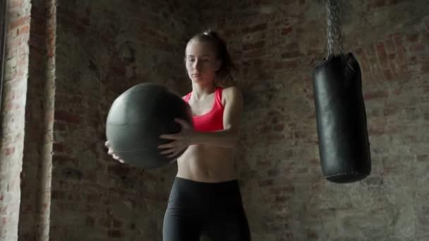 Fitnessfrau macht Übungen für die Presse für Fitness mit Fitnessball im Fitnessstudio