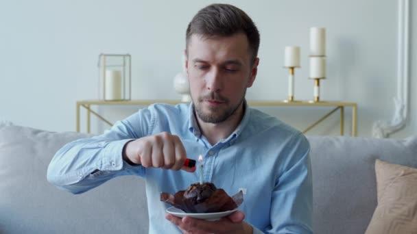 Ein Mann auf einem Sofa zündet eine Kerze auf einer kleinen Torte an