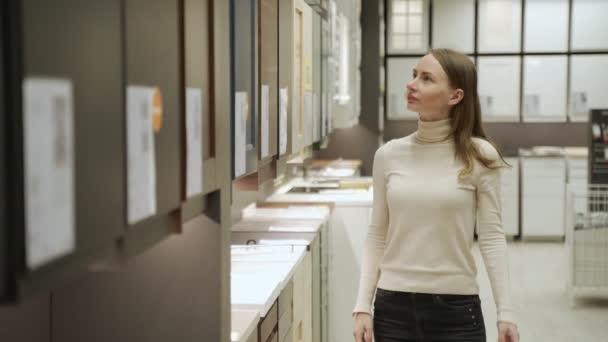 Mladá žena v obchodě výběr materiálu pro fasády na kuchyňský nábytek.