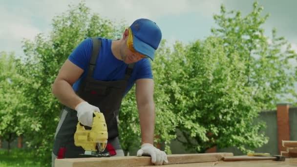 Tischler mit Mütze und Schutzbrille schneidet mit einer elektrischen Stichsäge ein Holzbrett.