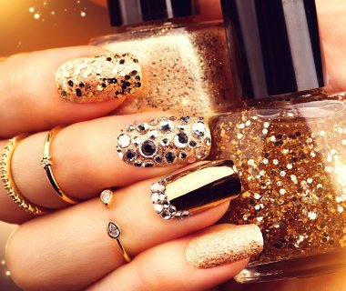 Golden manicure with gems and sparkles.