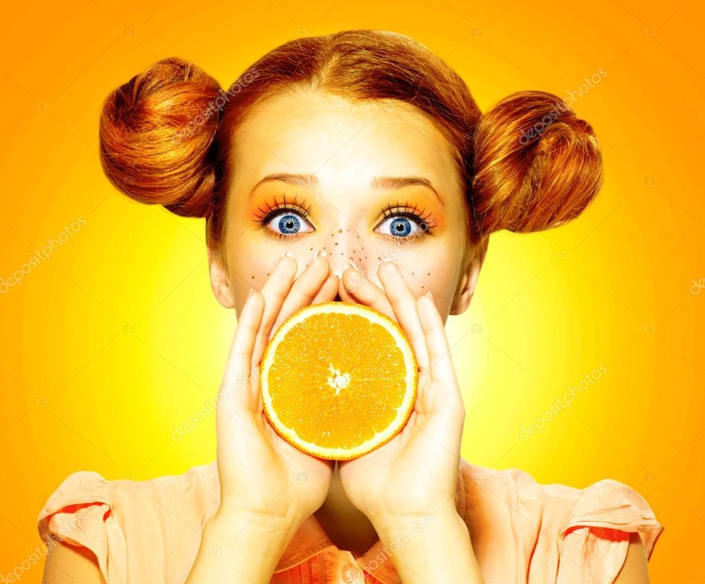 Girl takes juicy orange.