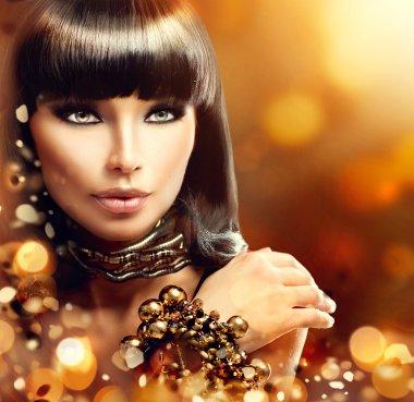 brunette girl with golden accessories