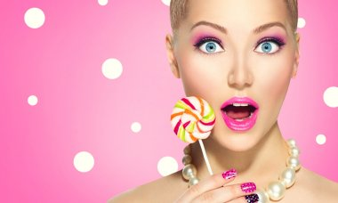 Funny girl eating lollipop