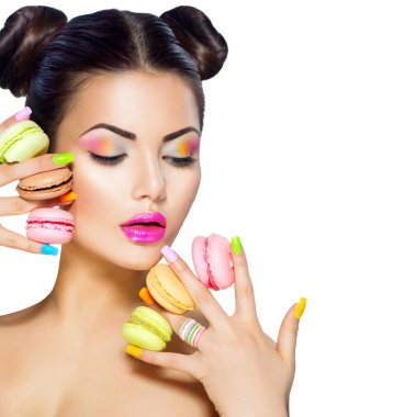 woman holding colorful macaroons