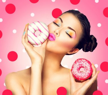 woman holding colorful donuts