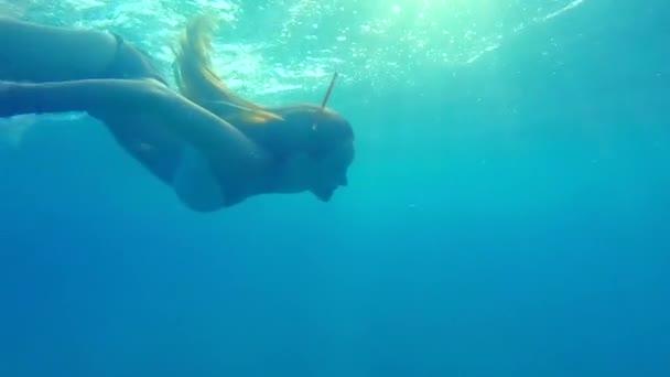Frau schwimmt unter Wasser im Meer