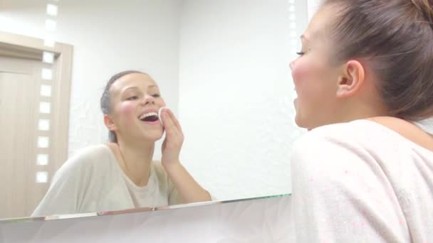 Teenage girl cleaning her face