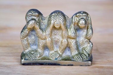 Brass statue of three monkeys isolated on wooden surface.