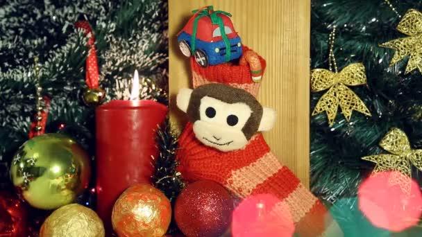 Karácsonyi háttér gyertyafénnyel és ajándékok a piros zokni a majom
