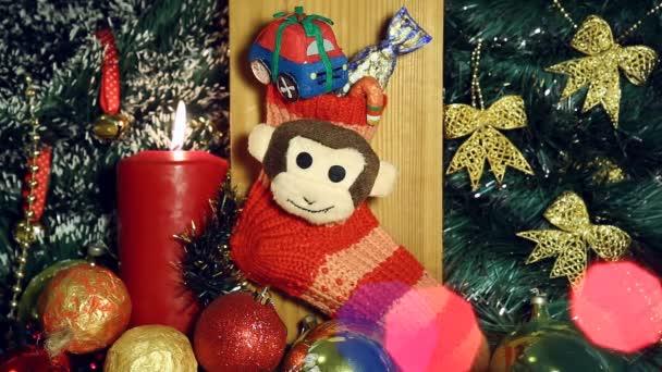 Vánoční pozadí s plameny svíček a opice na červené ponožky