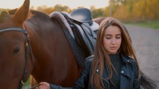 Krásná dívka kráčí vedle koně.