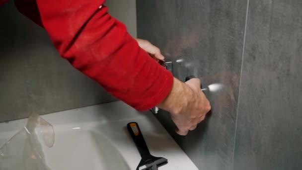 Ein Mann im Badezimmer installiert eine Duscharmatur an der Wand.