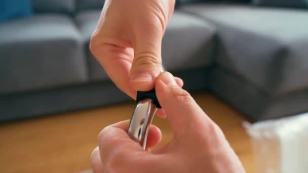 Männliche Hände schieben Kunststoffkissen über verchromte Stuhlbeine.