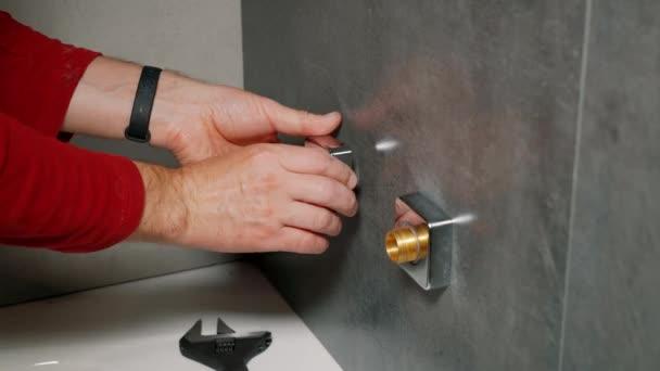 Ein Arbeiter installiert einen Duschhahn im Badezimmer.