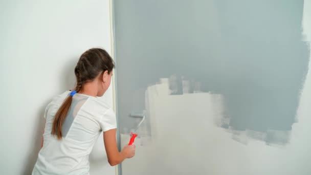 Ein junges Mädchen bemalt die Wand mit einem Roller grau. Renovierungen zu Hause.