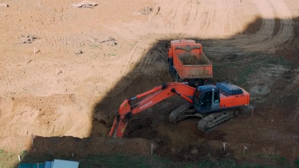Cheboksary, September 23, 2020. The excavator digs the ground and loads it into a dump truck. Site preparation for the construction of a residential building.