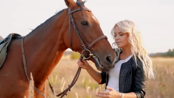 Schöne Blondine auf einem Feld neben einem Pferd.