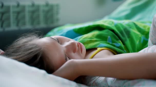 A young girl sleeps well in a comfortable cozy fresh bed on a soft pillow. Peaceful serene girl resting enjoying a healthy good sleep in the morning.