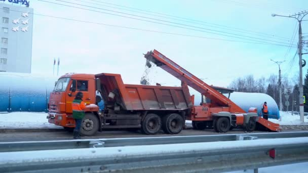 Russia, Cheboksary, March 2, 2021 : Snow cleaning tractor snow-removal machine loading pile of snow on a dump truck. Snow plow outdoors cleaning street city after blizzard or snowfall