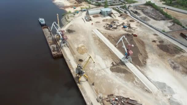 Large harbor cranes on the shore at the pier. Cargo port operation. Aerial photography.