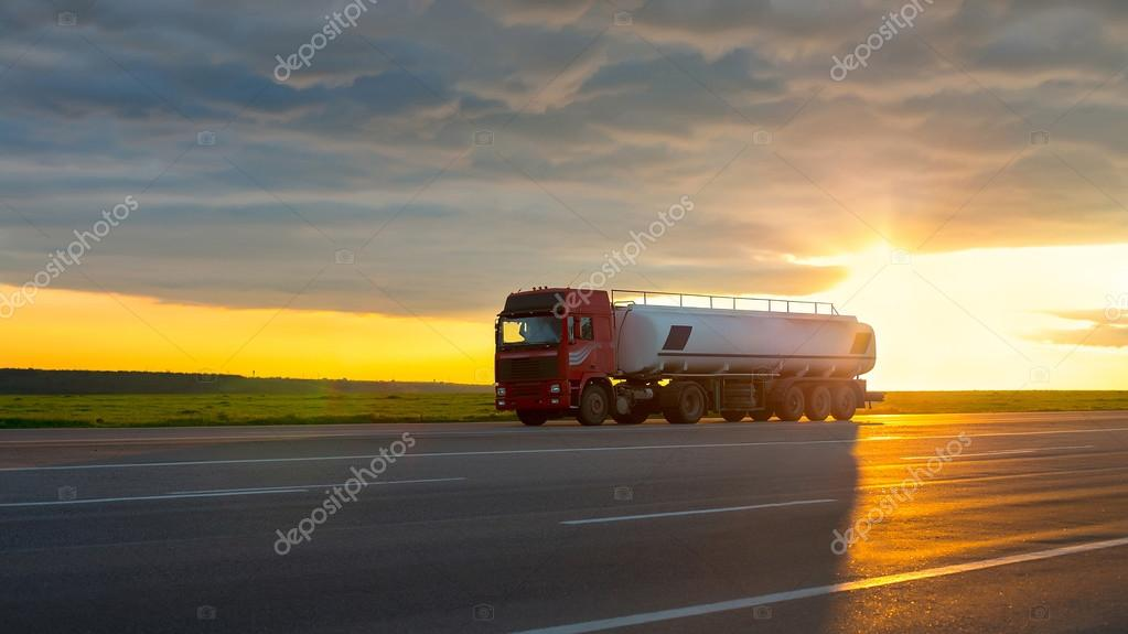 Truck moving on high-speed highway at sunset.