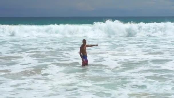 Muž plavat na tropické pláži a užívat si dovolenou. Teplé vlny oceánu omývají opálené mužské tělo. Relaxace na pobřeží s mořskou pláštěnkou v pozadí.