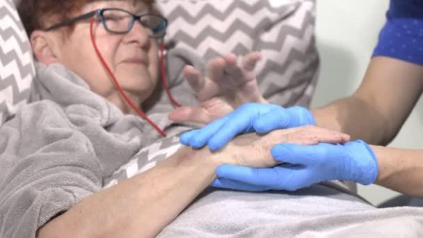 Pflegekraft an der Hand des Patienten, häuslicher Pflegedienst, Hilfe im Pflegeheim. Ältere Frau im Bett mit einer Krankenschwester zu Hause. Händchenhalten.