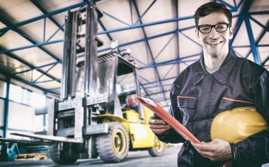 Smiling worker in protective uniform in front of forklift
