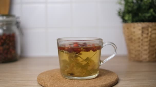 Brew tea from rosehip and lime blossom. Fruit tea. Brew in a cup. In the background of the kitchen-a pot with a flower. Bokeh. Blurred background.Cork board. 4k.