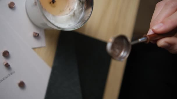 Melt a bronze wax stick on a spoon by tapping it. The spoon is placed over the hot orange flame of a candle on the wooden desk