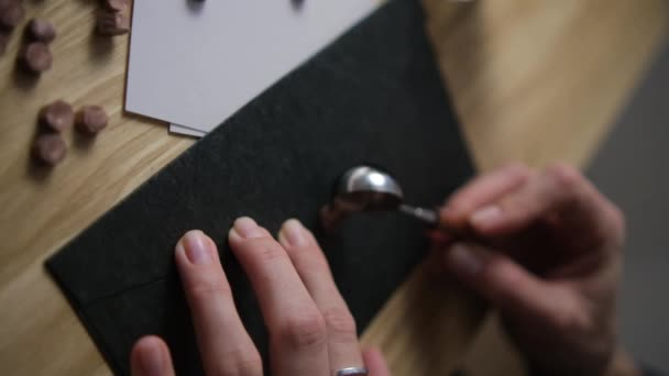 Pour hot wax on the envelope. Print paraffin. Blur. Selective focus. Black envelope and wood. Bronze Spoon.