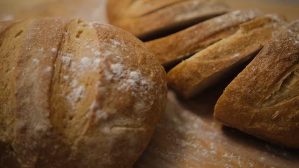 Brot in Scheiben geschnitten und frisch gebacken auf einem Holztisch. Mehl, Bäckerei. Der Kochvorgang wird in 4k-Auflösung festgehalten. Selektiver Fokus.