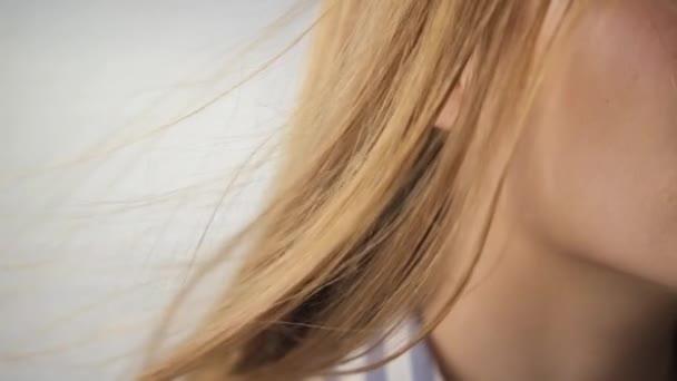 Detailní záběr rozvíjejících se, vznášejících se zrzavých vlasů. zpomalit. Z větru. Bílé rozmazané pozadí 240.