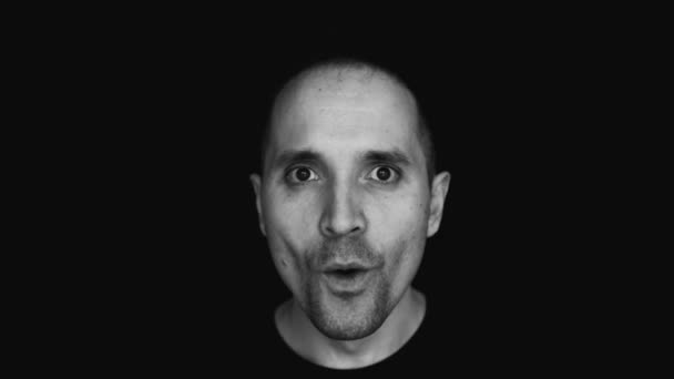 Černobílé video překvapeného muže. Překvapení. Překvapení. Reakce na dar. Úsměv. Černé pozadí.