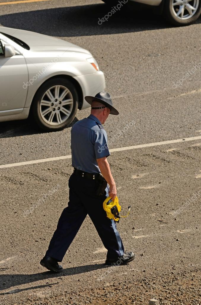 A Oregon State Police Trooper investigating a motor vehicle accident