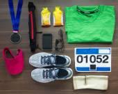 Fényképek Top View futócipő, Marathon rajtszámot (szám), érem, futók felszerelés és energia gél a fa háttér, Sport, Fitness és egészséges életmód fogalma