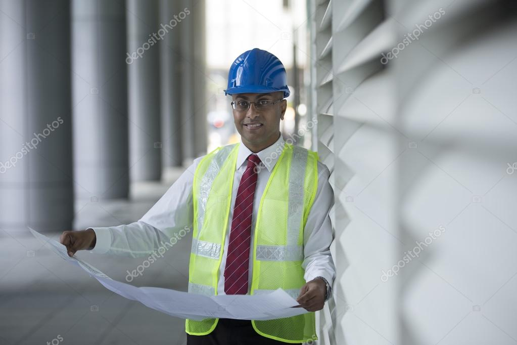 Indian engineer checking plans