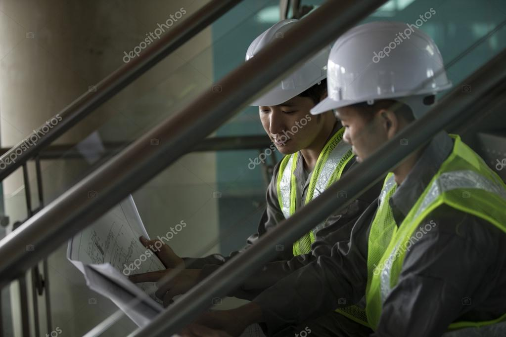 Chinese industrial engineers looking at plans