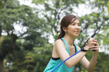 Asian woman exercising with resistance band.