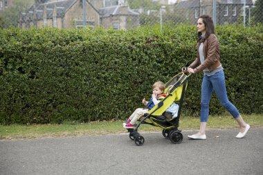 Mum pushing her toddler in pram
