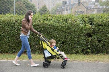 Mum talking on phone  pushing toddler in pram