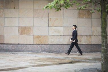 asian businessman walking in city